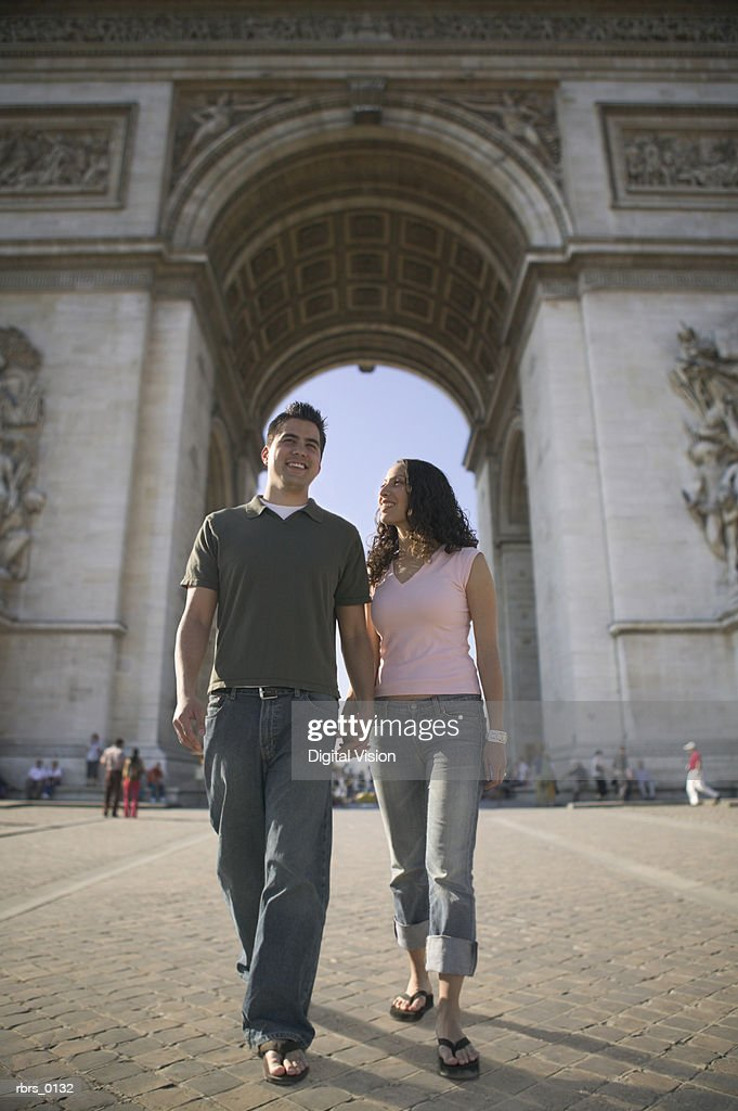 wide shot of a young adult couple as they walk hand in hand while sightseeing in paris : Foto de stock