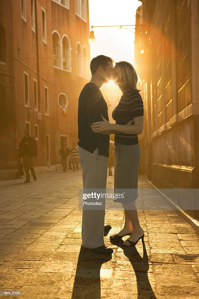wide shot of a young adult couple kissing at sunset : Stockfoto