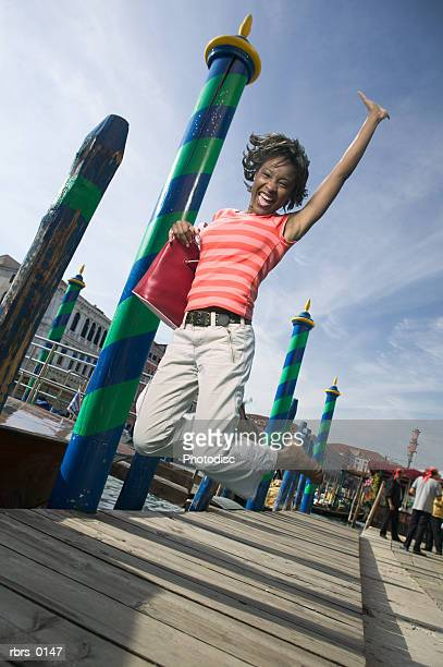 wide shot of a young adult female as she jumps up on a pier - pedal pushers stock pictures, royalty-free photos & images