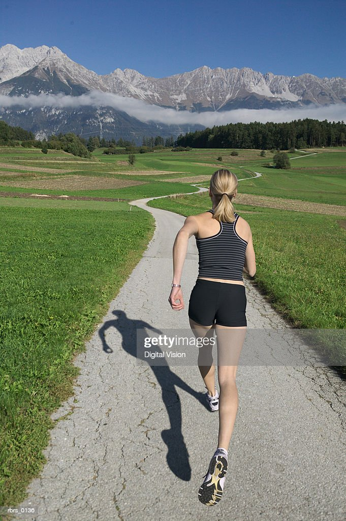 wide shot of a young female jogger as she runs down a long path near a mountain range : Foto de stock