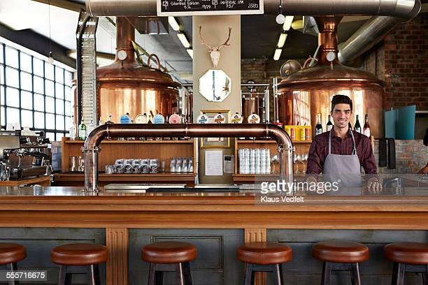 wide shot of bartender at cool microbrewery - comptoir de bar photos et images de collection
