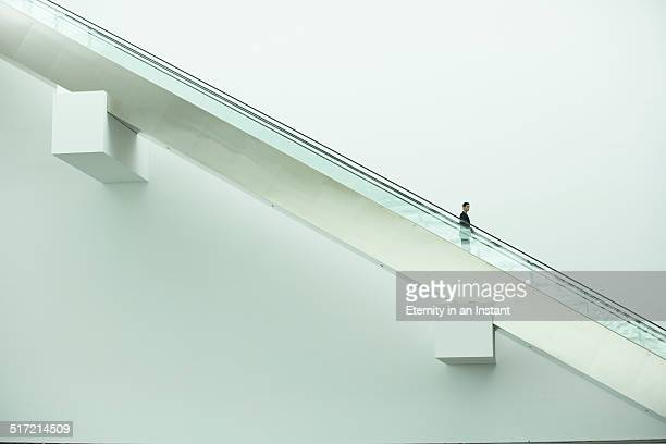 Wide shot of businessman going down an escalator