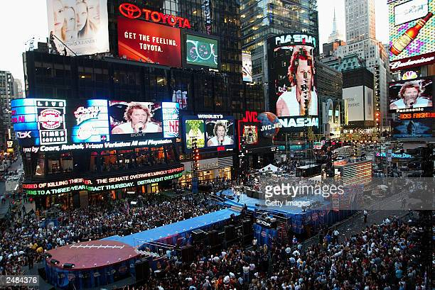 Wide shot of crowds watching rock band Bon Jovi on stage and on Jumbotron screens during 'Countdown to Kickoff: The NFL Times Square Concert' to...