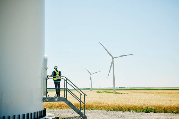 Wide shot of engineer preparing to enter wind turbine for inspection