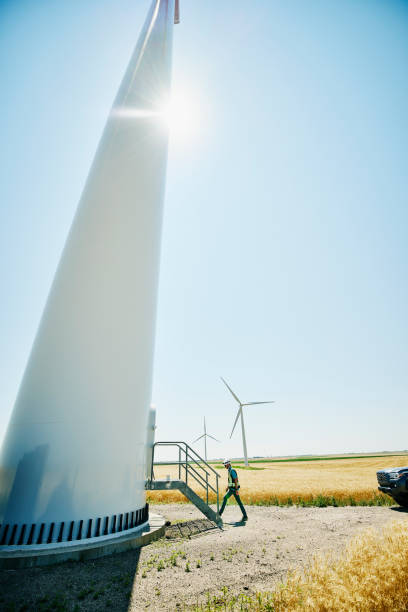 Wide shot of engineer preparing to inspect wind turbine on summer afternoon