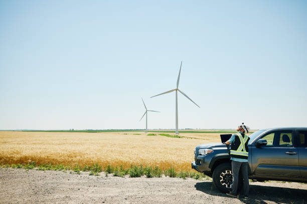 Wide shot of engineer using laptop on hood of truck while inspecting wind turbines