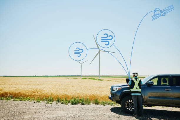 Wide shot of engineer using laptop on hood of truck while inspecting wind turbines with wind and satellite communication illustration overlay
