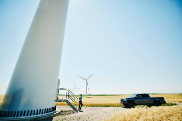 Wide shot of engineer walking away from wind turbine after inspection