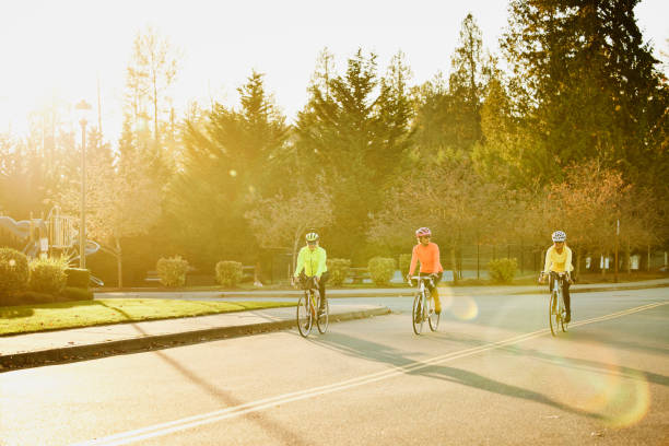 Wide shot of mature female friends on road bike ride on fall evening