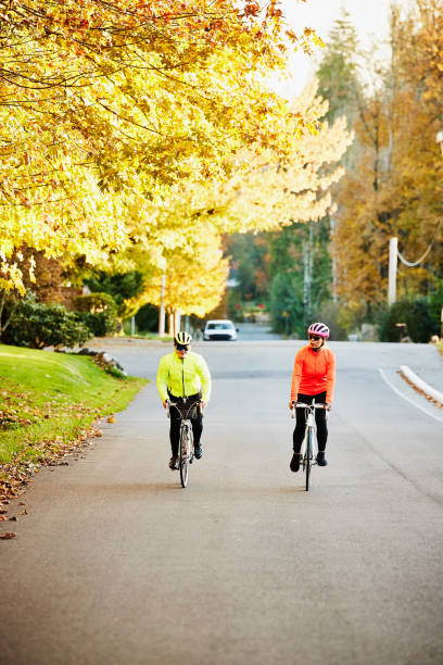 Wide shot of mature female friends on road bike ride on fall afternoon