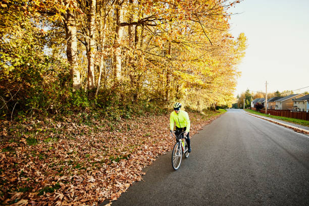 Wide shot of mature woman riding road bike on fall afternoon