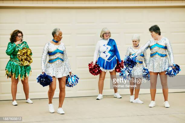 wide shot of senior female cheerleaders practicing in driveway of home on summer morning - mini dress stock pictures, royalty-free photos & images
