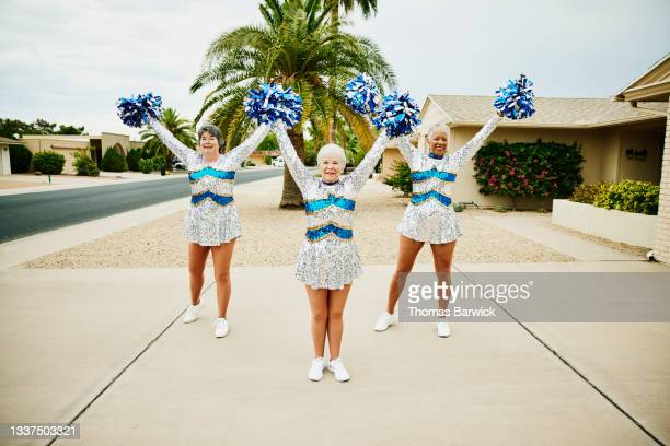 wide shot of senior female cheerleaders practicing in driveway on summer morning - mini dress stock pictures, royalty-free photos & images