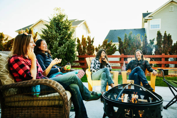 Wide shot of smiling and laughing female friends hanging out by fire in backyard