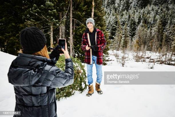 wide shot of smiling teenage boy having picture taken by sister after cutting christmas tree in snow covered forest - embellished jacket stock pictures, royalty-free photos & images