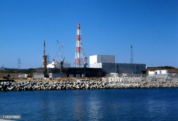 Wide shot of the Fukushima Daiichi Nuclear Power Plant, under construction on a sunny day, with a seawall and the Pacific Ocean in the foreground,...