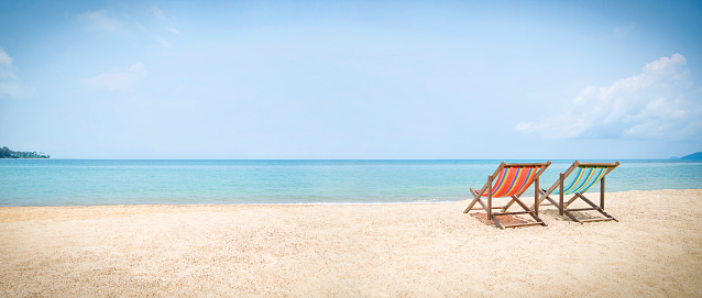 Wide shot of two deckchairs facing out to sea on idyllic beach. 996272632