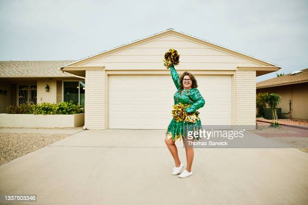 wide shot portrait of smiling mature female cheerleader posing in front of home - mini dress stock pictures, royalty-free photos & images
