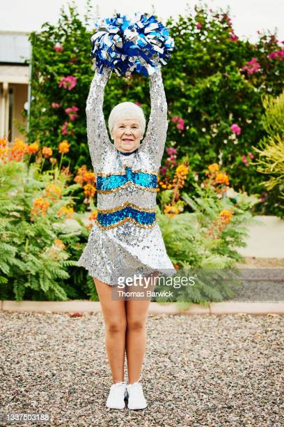 wide shot portrait of smiling senior female cheerleader in backyard garden - fringe dress stock pictures, royalty-free photos & images