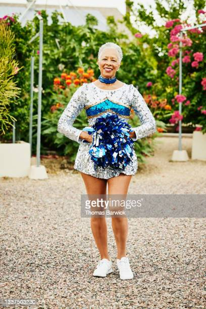 wide shot portrait of smiling senior female cheerleader in backyard garden - mini dress stock pictures, royalty-free photos & images