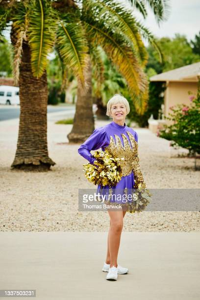 wide shot portrait of smiling senior female cheerleader posing in front of home - fringe dress stock pictures, royalty-free photos & images