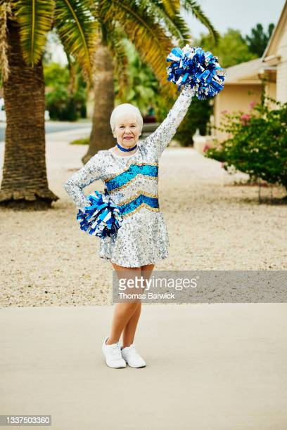 wide shot portrait of smiling senior female cheerleader posing in front of home - mini dress stock pictures, royalty-free photos & images
