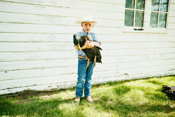 Wide shot portrait of young boy holding duck outside of chicken coop on farm on summer morning