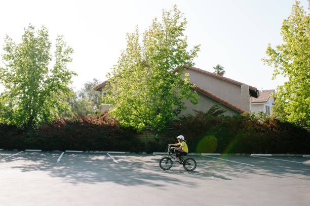 Wide shot profile of girl riding her bike in a parking lot