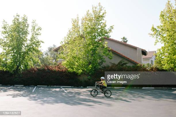 wide shot profile of girl riding her bike in a parking lot - サウザンドオークス ストックフォトと画像
