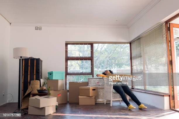 wide shot young woman lies relaxing in a chair taking a break from moving in to her new house - wide stock pictures, royalty-free photos & images
