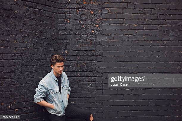 wide view of stylish man on a brick wall