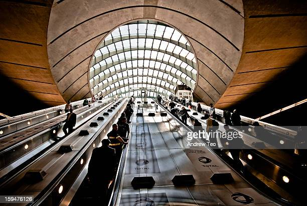 Wide-angle shot of the set of 4 escalators at Canary Wharf underground station in London. Commuters and tourists ascend and descend on the stairways....