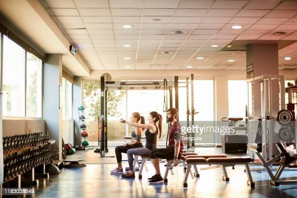 wide-angle view of a gym with people lifting weights. - wide shot stock pictures, royalty-free photos & images