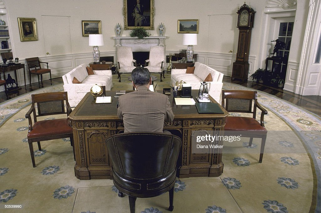 A wide-angle view of President Ronald Reagan sitting at his desk in the Oval Office of the White House.