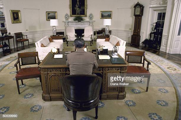A wideangle view of President Ronald Reagan sitting at his desk in the Oval Office of the White House