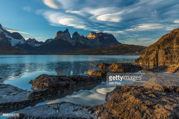 Wideangle view of the Cuernos del Paine and Monte Almirante Nieto with rocks and Lake Pehoe in the foreground Lenticular clouds are beginning to form...