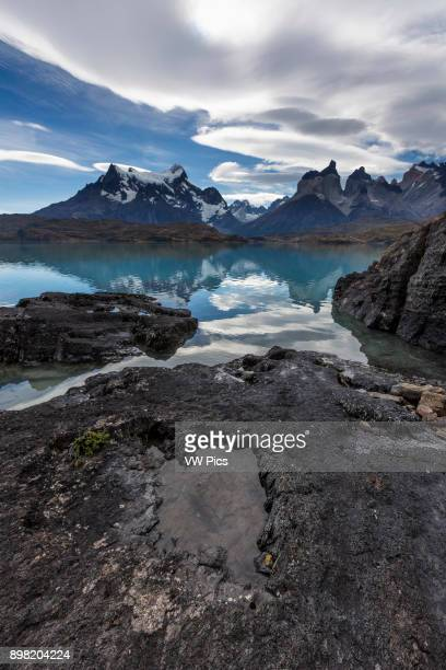 Wideangle view of the Paine Masif with rocks and Lake Pehoe in the foreground From left to right _ Cerro Paine Grande the Cuernos del Paine or the...