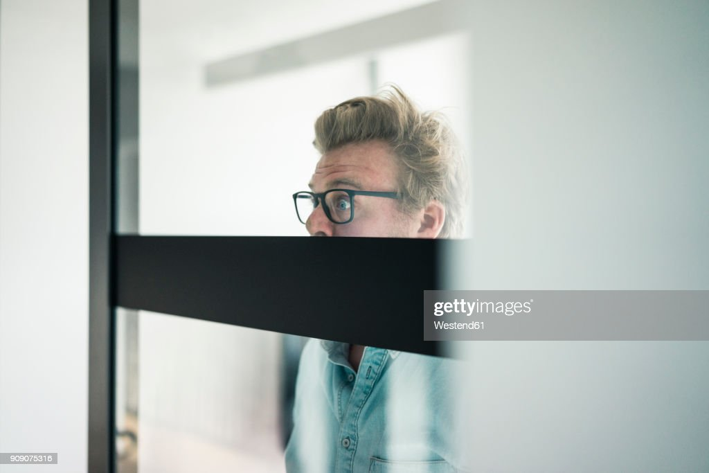 Wide-eyed businessman behind glass pane in office : Stock Photo