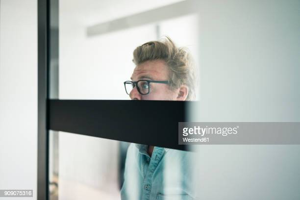 wide-eyed businessman behind glass pane in office - überraschung stock-fotos und bilder