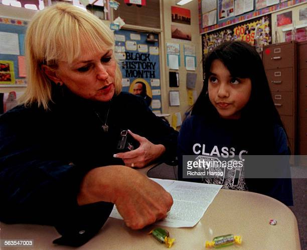 A wide–eyed Marie Ortiz right pauses a moment as she tries to figure out a word during a reading exercise with teacher Marilyn Barnett during the...