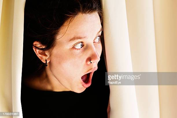 Wide-eyed, shocked woman peeping out: what are the neighbours doing?