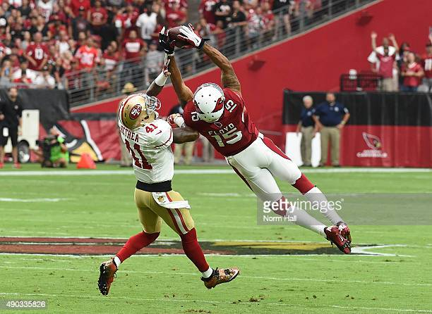 Wider receiver Michael Floyd of the Arizona Cardinals makes a leaping catch over strong safety Antoine Bethea of the San Francisco 49ers during the...