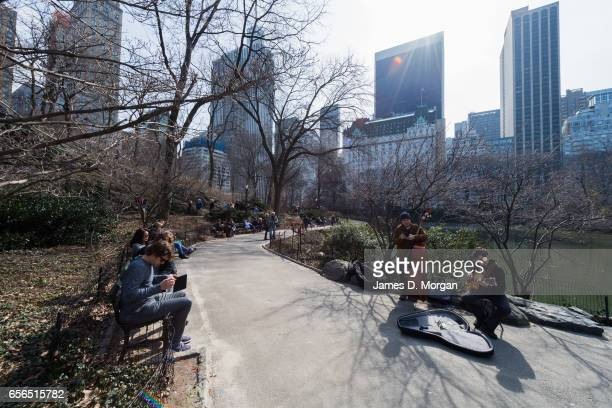 Wides shots of Central Park featuring people sitting at benches by the pond and tall skyscrapers outlining Now Yorks city skyline in New York City on...