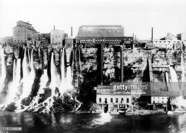 Wide-shot of several industrial factories built on the edge of waterfalls in order to harness hydroelectric power, Niagara Falls, New York, 1890....