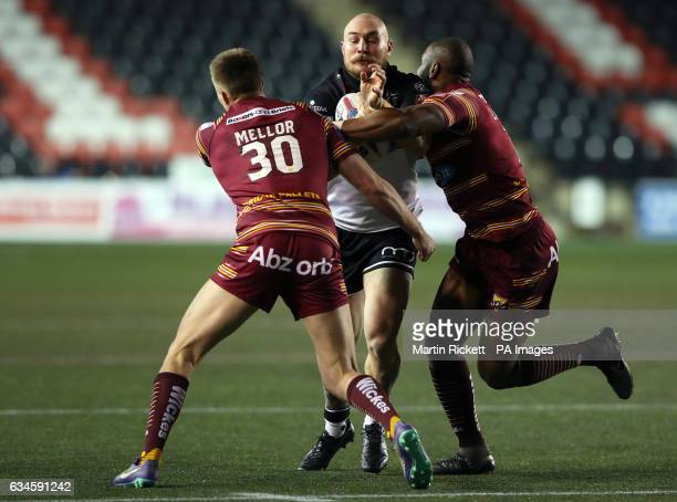 Widnes Vikings' Gil Dudson is tackled by Huddersfield Giants' Michael Lawrence and Alex Mellor during the Super League match at the Select Security...