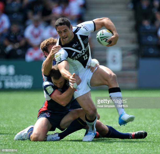 Widnes Vikings' Hep Cahill is tackled by St Helens' Josh Perry and James Roby