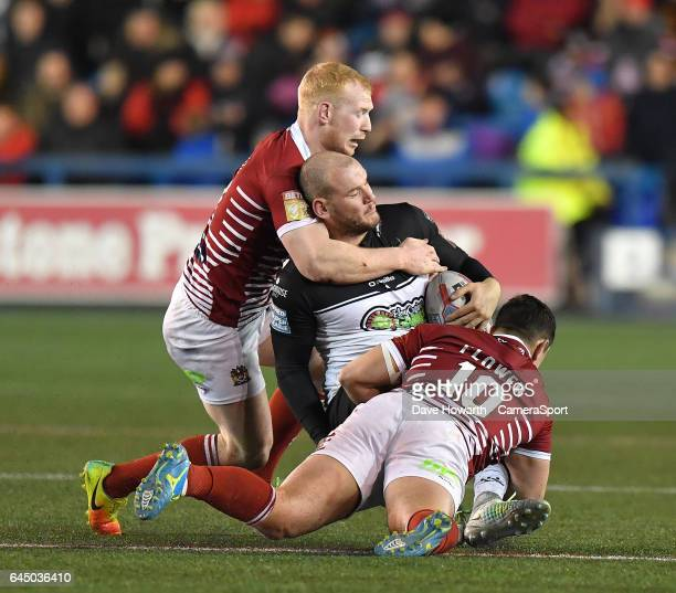 Widnes Vikings' Jack Buchanan is tackled by Wigan Warriors' Ben Flower and Liam Farrell during the Betfred Super League Round 2 match between Widnes...