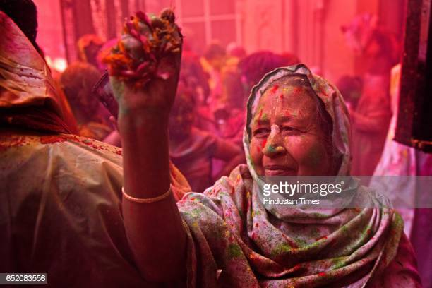 A widow celebrating Holi festival with the flowers and colours at Gopinath temple Vrindavan on March 9 2017 in Mumbai India Holi is a Hindu spring...