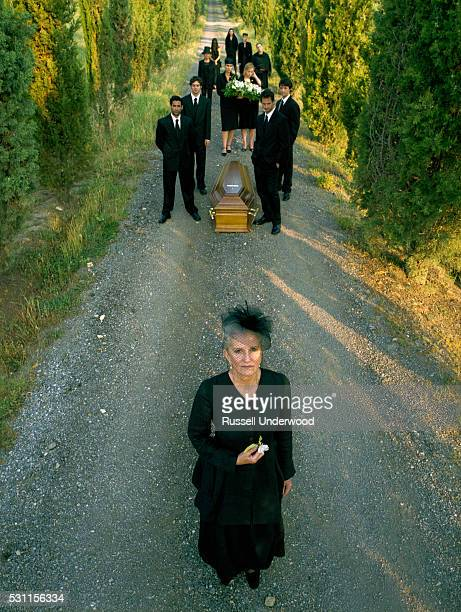 widow leading coffin procession - pallbearer stock photos and pictures