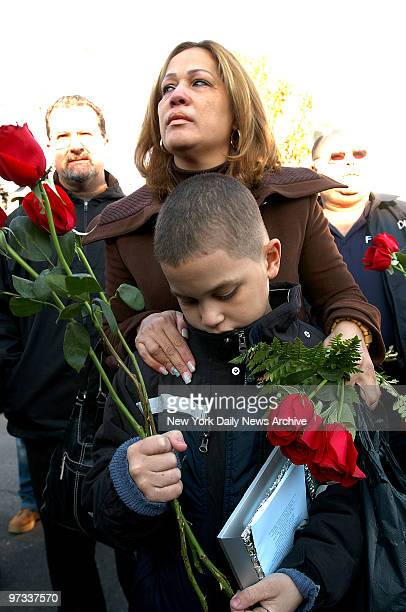 Widow Olivia Sanchez who lost her husband Elvis Sanchez comforts her son 9yearold Elvis Sanchez Jr during a memorial service this morning on the...